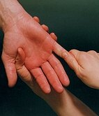 Photo of therapist massaging client's hand